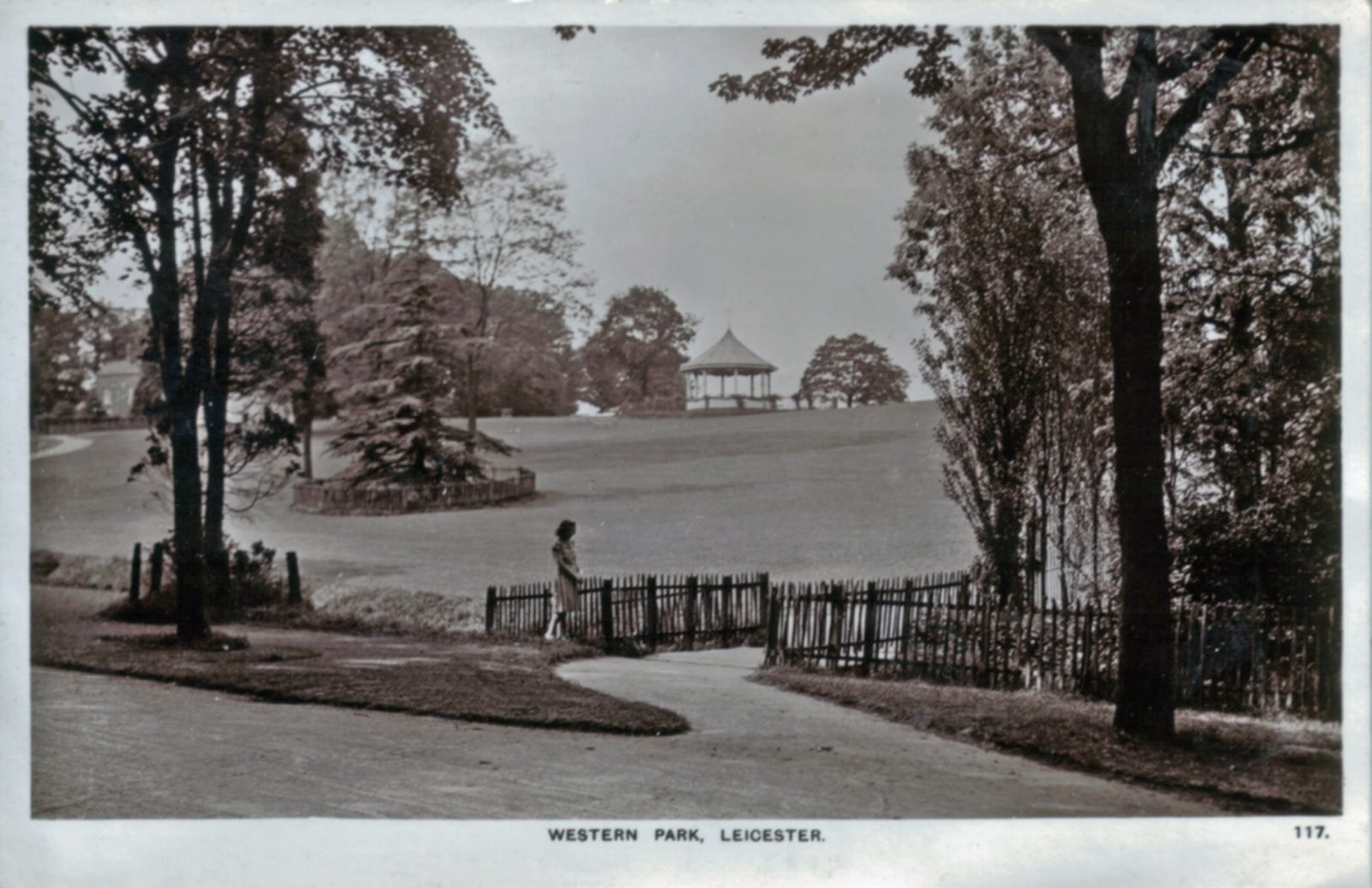 Western Park, Leicester. Undated: General view. Female figure on bridge. Bandstand in background. Franked 1954 (File:1088)